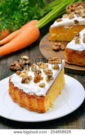 Homemade piece of carrot cake with icing decorated walnut