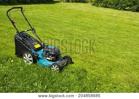 Mowing lawns Lawn mower on green grass mower grass equipment mowing gardener care work tool close up view sunny day