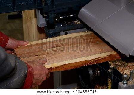 Carpenter planing with planing machine board made of plum