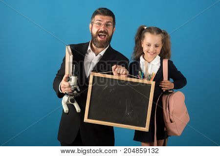 Man and girl in school uniform. Studying and alternative education concept. Teacher and schoolgirl with cheerful faces on blue background. Kid and tutor hold microscope blackboard bag and stationery