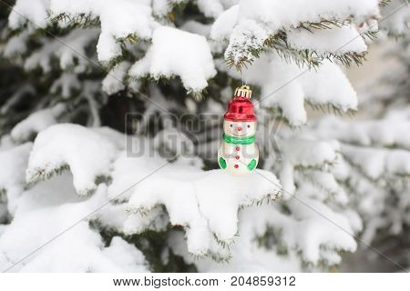 Snowman Toy Hanging On Branch Covered With Snow