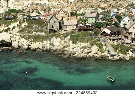 Papay village on Malta, old wooden houses and blue sea