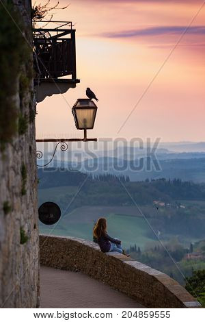 San Gimignano. girl looking at the tuscanian landscape with the hills and cypresses at dawn