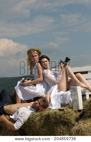 Friends relaxing on sunny day on blue sky. Summer vacation concept. Man or macho lying on hay. Brunette woman with camera. Blond girl with vintage typewriter.