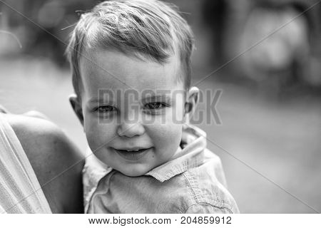Cute happy baby boy little child with blond hair in blue shirt smiling on summer sunny day outdoors on natural background