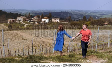Man and woman stands near a vineyard and a typical Tuscan landscape behind them. Tuscany Italy