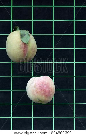 Two ripe peaches on a metal grid