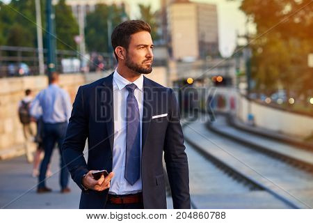 A handsome young businessman standing and waiting at the tramstop in the sunset