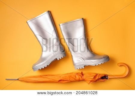 From above view of stylish silver gumboots and umbrella on orange background. Top view. Flat lay.