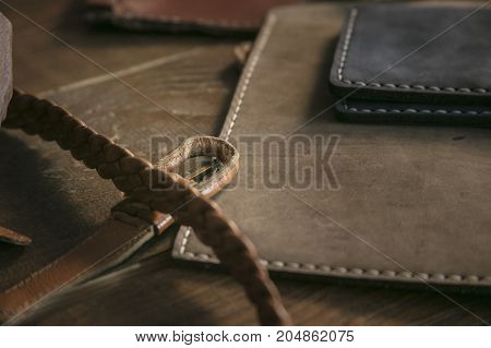 Original product. Close up of few handmade purses and braided leather strap on wooden table in leather workshop. Creative handmade business product