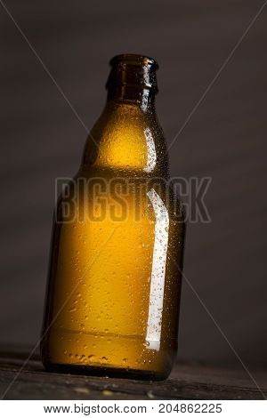 Well-chilled wet beer bottle placed on a rustic wooden table in a bar. Selective focus on the upper part of the bottle