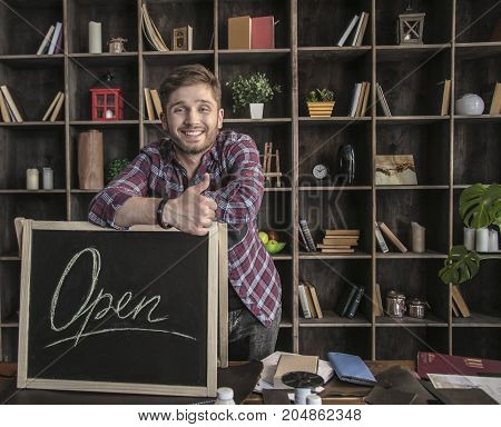 Opening workshop. Young smiling man leather maker standing near open sign at wooden table in leather workshop. Creative business in cozy home workshop