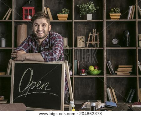 Nice workshop. Young smiling man leather worker standing near open sign at wooden table with tools in leather workshop and rejoices. Business work in studio