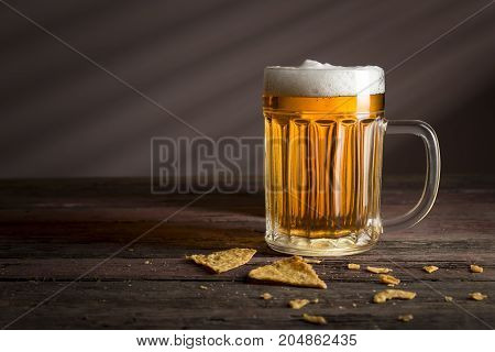 Mug of cold pale beer placed on a burlap cover with some tortilla chips on a rustic wooden table. Selective focus