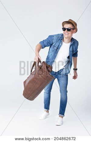 Handsome young man in denim holding leather bag and running on grey background