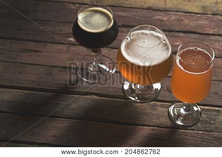 Pale dark and red fruit beer in three different beer glasses on a rustic wooden table. Selective focus
