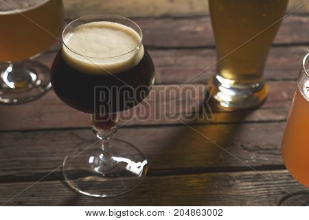Pale dark unfiltered pale and red fruit beer in four different beer glasses on a rustic wooden table. Selective focus on the foam