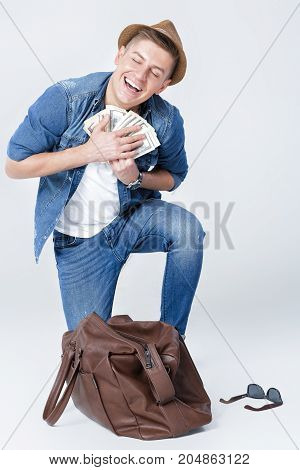 young happy man in a hat found money in a leather bag. man with dollar bills