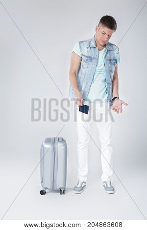 frustration young man in denim vest with suitcase and with passport against grey background