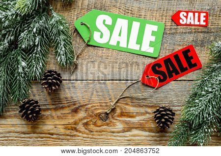 Winter sale. Sale labels near spruce branches on wooden background top view.