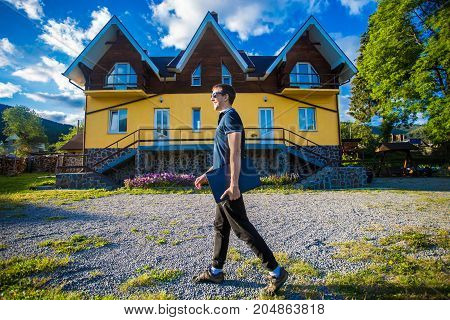 Happy young businessman in sunglasses bought a big home for his family. Man standing with laptop near her new home
