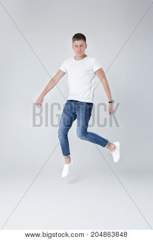 young happy handsome man in jeans and  white t-shirt jumping