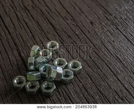 Close up nuts(fastener,tools)on dark brown wooden background