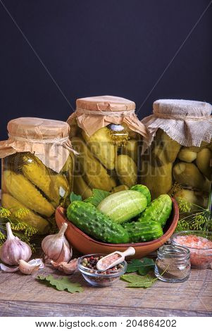 Salted cucumbers. Spices and herbs for making pickles on wooden background. Rustic stile.