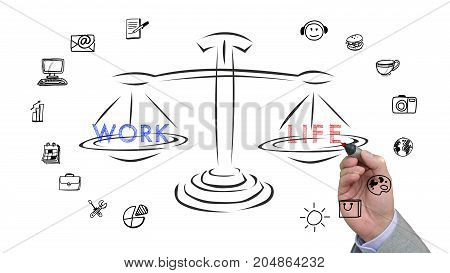 Hand is drawing a sketch of a work life balance on a scale with icons on white