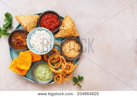 Indian vegetable snacks and  dips in small bowls, top view, blank space