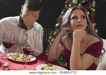 Beautiful young couple sitting at a table having a fight over a romantic Christmas dinner