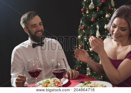 Beautiful couple sitting at a table having a romantic Christmas dinner and enjoying their time together. Focus on the guy
