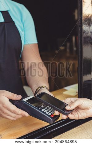 Person paying pay through smartphone using NFC technology in outdoor cafe