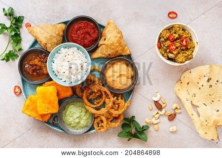 Indian Vegetarian Thali and poppadom on rustic surface. Top view, blank space