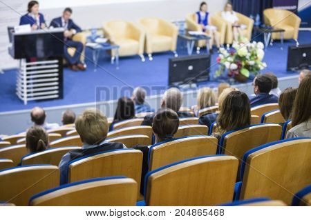 Business Conferences and People Concepts and Ideas. Group of People Attending Conference and Listening to the Host Speaker On Stage. Back View. Horizontal Image Composition