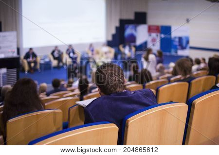 Business and Entrepreneurship Ideas. Group of Professionals Giving a Talk on Stage in Front of the Audience at Business Meeting or Conference. Back View of the Listeners.Horizontal Image