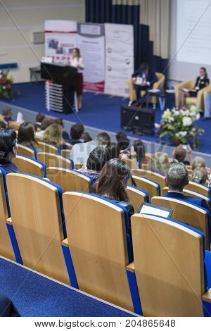 Business Ideas and Concepts. Female Host Speaking at Stage In Front of The Audience During Business Conference in Large Congress Hall. Ideas Entrepreneurship.Vertical image