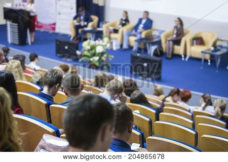 Business Ideas and Concepts. Female Host Speaking at Stage In Front of The Audience During Business Conference in Large Congress Hall. Ideas Entrepreneurship. Horizontal image