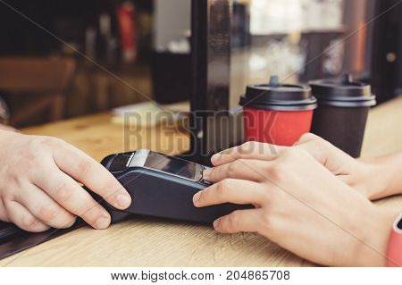 Person using pos terminal at the outdoor cafe
