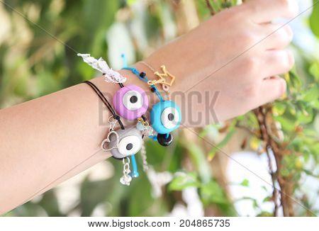 woman hand wearing colorful evil eye bracelets - greek jewelry advertisement