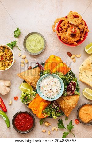 Spicy vegetable and meat  Indian snacks with jeera rice, various salads and sauces on rustic surface. Top view, blank space
