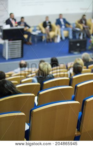 Business Concepts. Group of Hosts Sitting on Stage At Table During a Conference. Male Lecturer Giving a Talk on Stage in Front of the Audience.Vertical Image Orientation