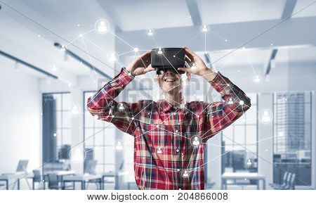 Young man with virtual reality headset or 3d glasses over connection background . Mixed media