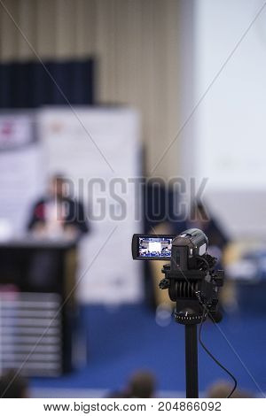 Back View of Compact Videocamera. Positioned Against Blurred Background with Host Speaking on stage. Vertical Image