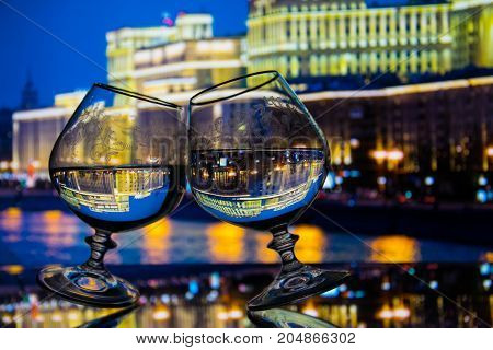 Two glasses with liquid on glass table night city background