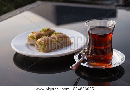 East dessert baklava. puff pastry with honey and pistachio and turkish tea on the black table in cafe. glass of turkish tea on saucer with spoon and four pieces of baklava on the white plate.