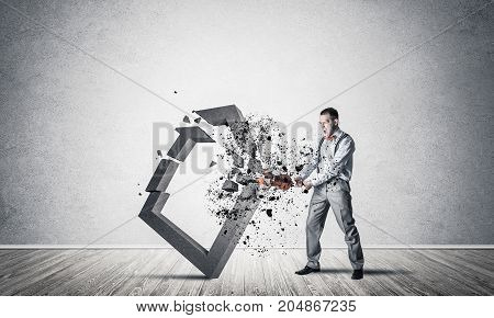 Determined businessman jumping and breaking with violin house concrete figure