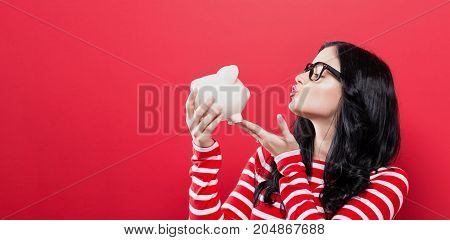 Young woman with a piggy bank on a red background