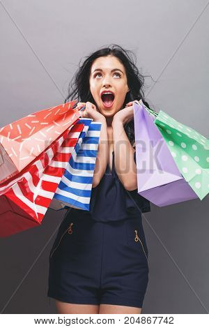 Happy young woman holding shopping bags on a gray background
