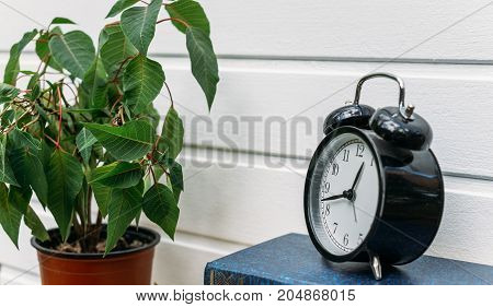 Retro alarm clock on white wooden wall background